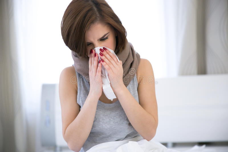 Woman caught cold. sneezing into tissue stock photography