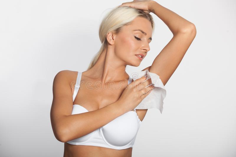Woman celaning armpit with wet wipes stock photography