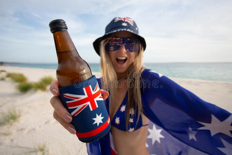 Woman celebrate Australia Day with beer. A revelling woman holding a beer on the beach celebrates Australia Day or supports Australian sport enthusiast fan stock images