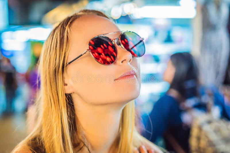 Woman celebrate Chinese New Year look at Chinese red lanterns. Chinese lanterns are reflected in glasses royalty free stock photos