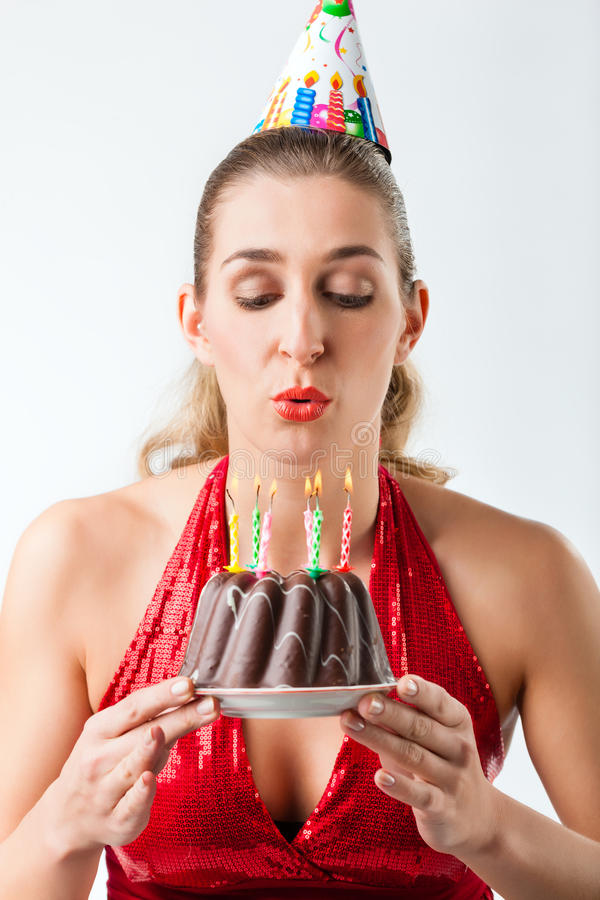 Woman celebrating birthday with cake blowing candles out royalty free stock image