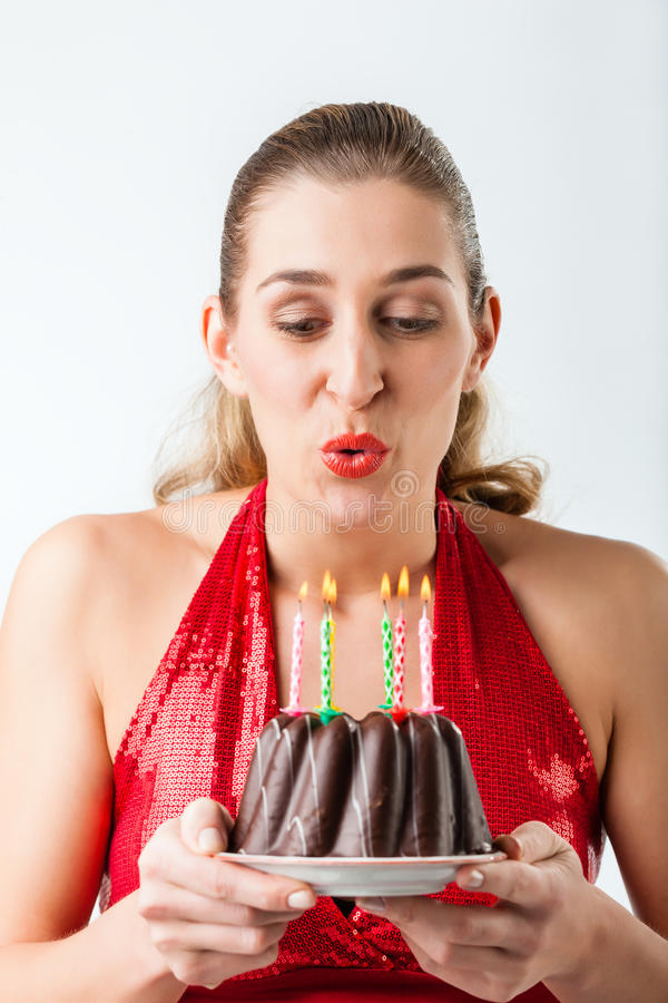 Woman celebrating birthday with cake blowing candles out royalty free stock images