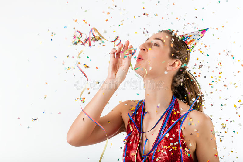 Woman celebrating birthday with streamer and party hat royalty free stock photography