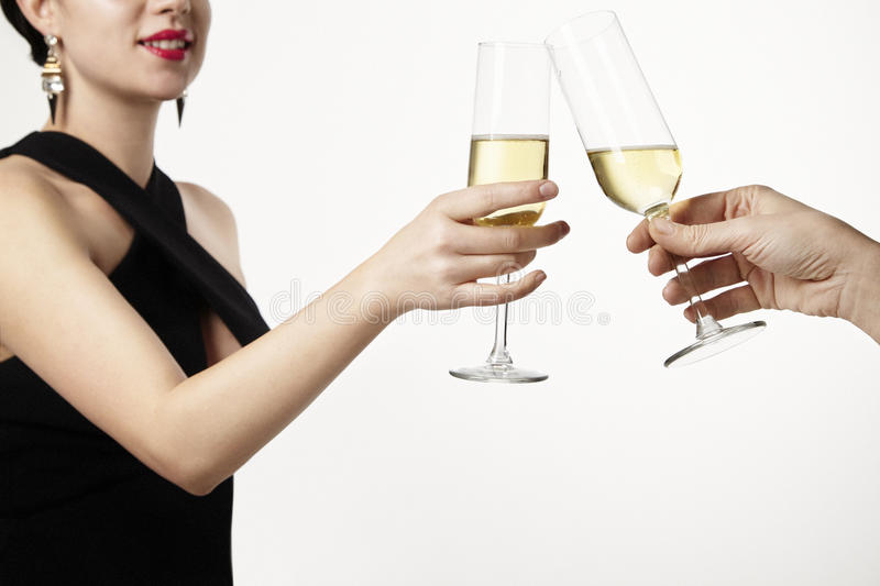 Woman celebrating and clang glasses together with champagne. Par. Ty concept. White background stock images