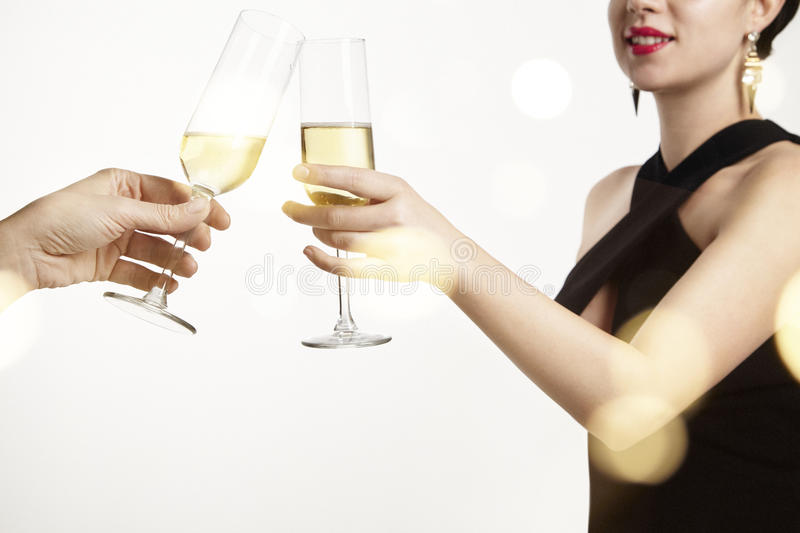 Woman celebrating and clang glasses together with champagne. White background with flares royalty free stock images