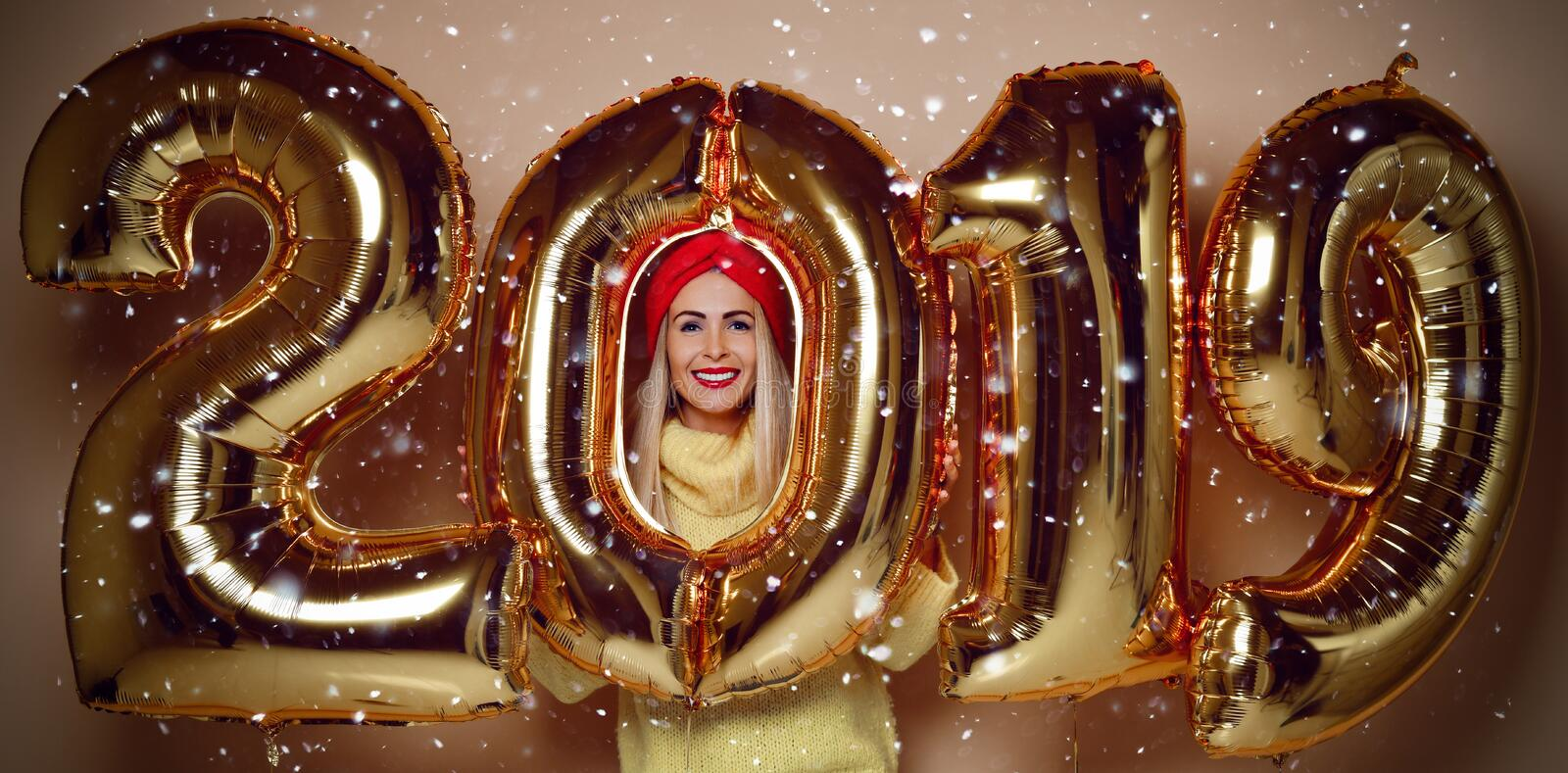 Woman celebrating New Year xmas party happy laughing in yellow sweater blouse with 2019 gold balloons stock image