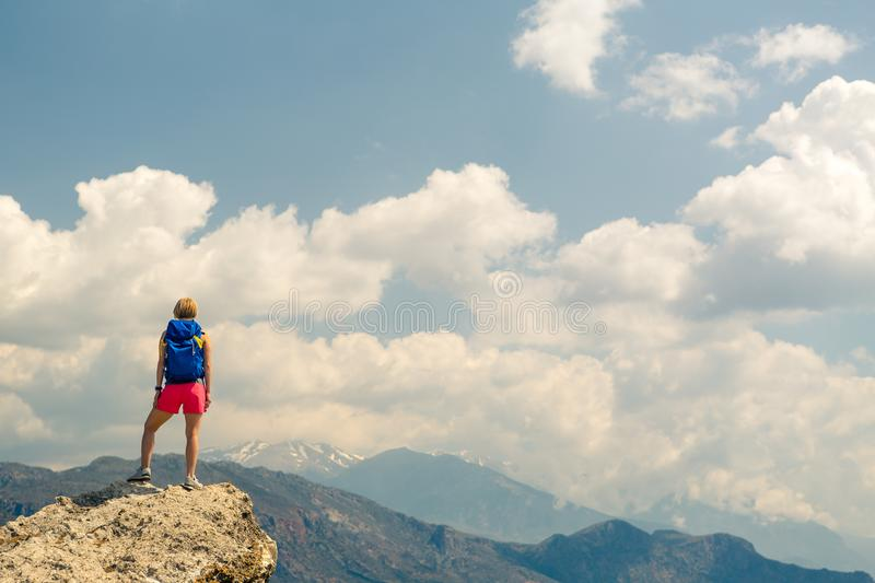 Woman looking and celebrating sunrise and landscape. Woman celebrating or praying in beautiful inspiring mountains sunrise. Girl hiker on mountain top hiking or stock photos