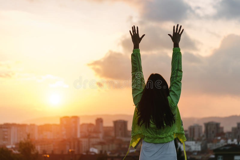 Woman celebrating sport and fitness lifestyle success. Back view of a happy woman celebrating sport goals and fitness lifestyle success. Female athlete raising stock photo
