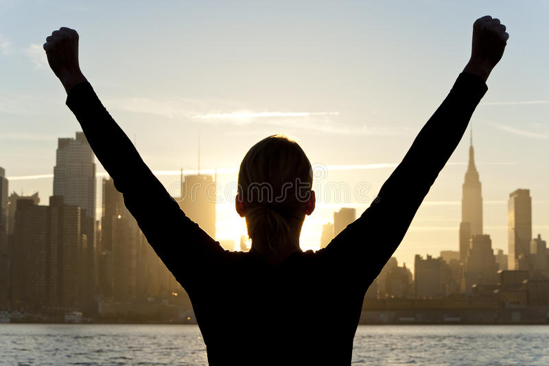 Woman Celebrating at Sunrise in New York City. Rear view silhouette of a woman celebrating arms raised at sunrise in front of the Manhattan skyline New York City stock photos