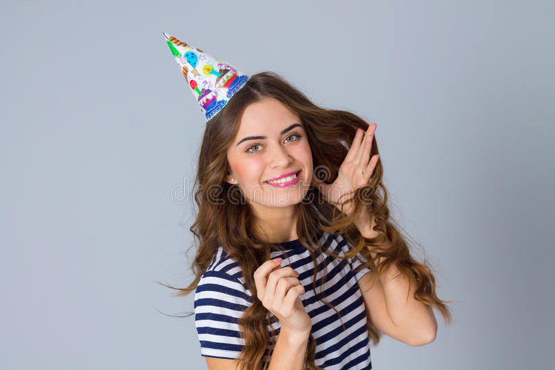 Woman in celebration cap fixing hair stock photography