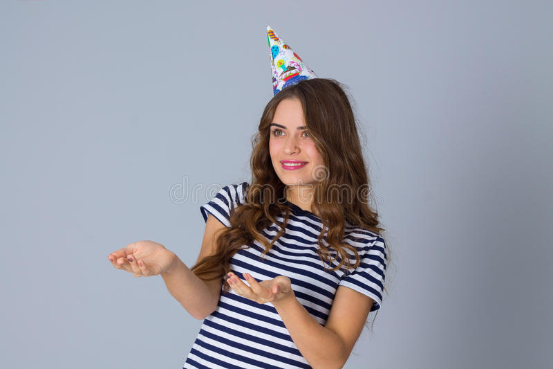 Woman in celebration cap holding hands in front of her stock photos