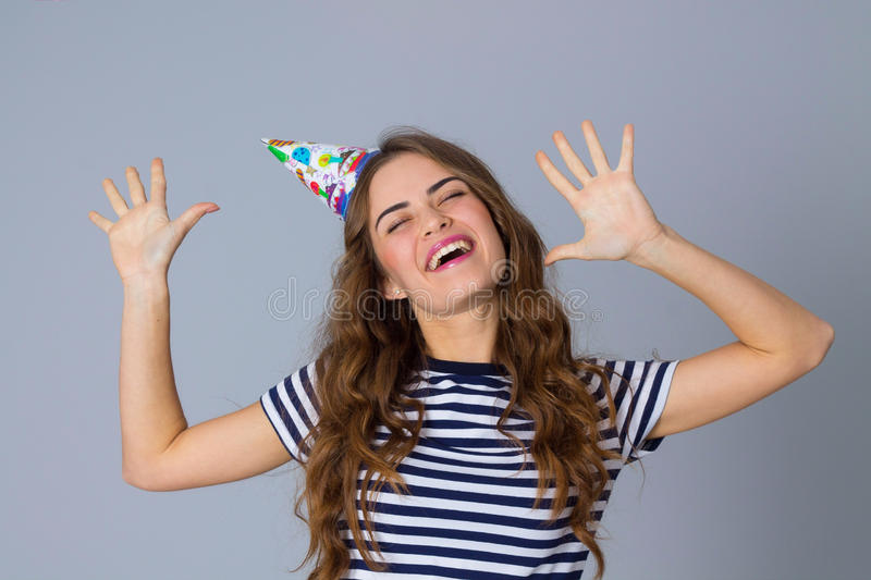 Woman in celebration cap holding hands up royalty free stock photo