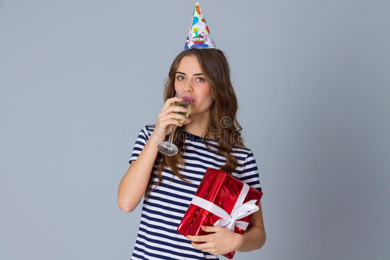Woman in celebration cap holding a present and drinking stock photography
