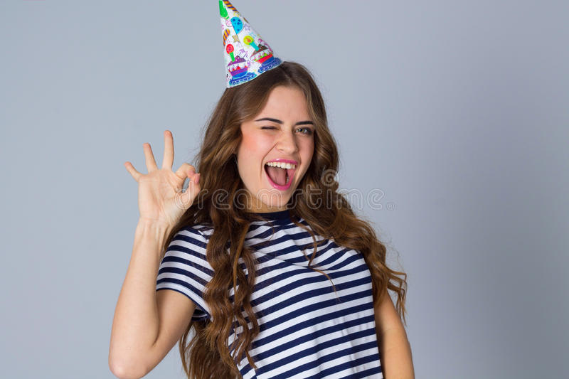 Woman in celebration cap showing okay royalty free stock photography