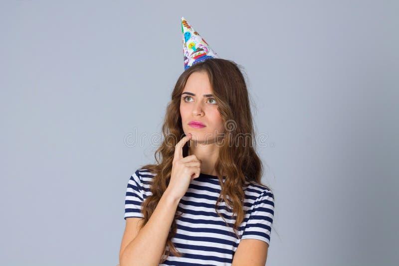 Woman in celebration cap thinking stock photo