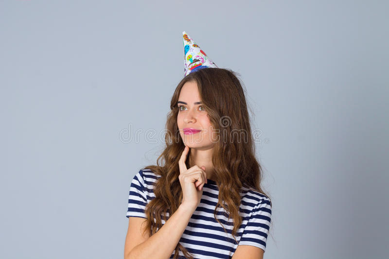 Woman in celebration cap thinking stock photography