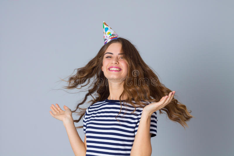 Woman in celebration cap whirling. Young positive woman in stripped T-shirt and celebration cap whirling on grey background in studio stock photography