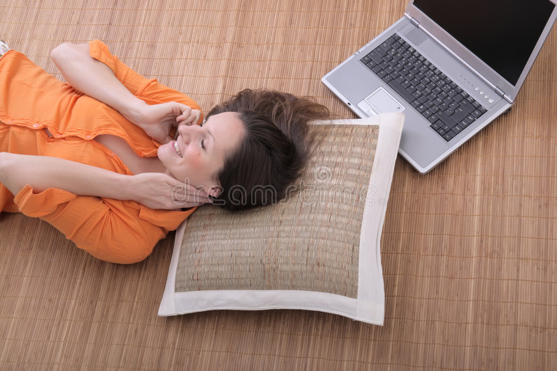Woman on the cell phone. Beautiful young woman with laptop talking on the cell phone royalty free stock photos