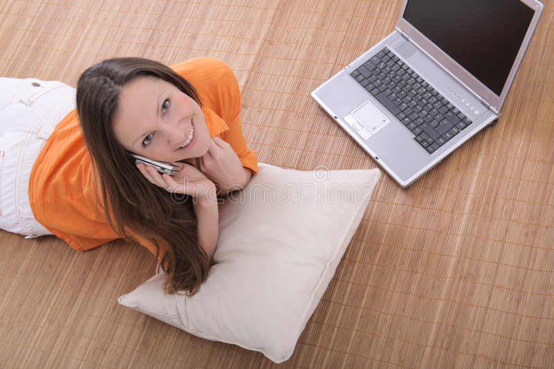 Woman on the cell phone. Beautiful young woman with laptop talking on the cell phone stock images