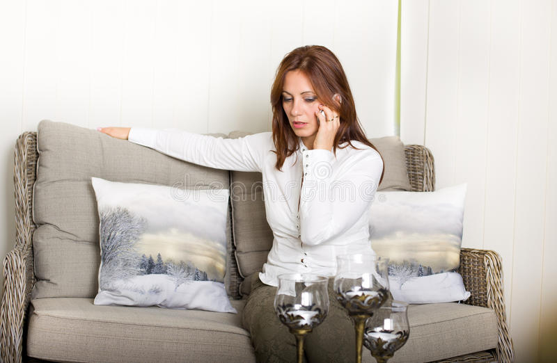 Woman with cell phone. Attractive middle aged woman sitting in living room and talking on cell phone royalty free stock photo