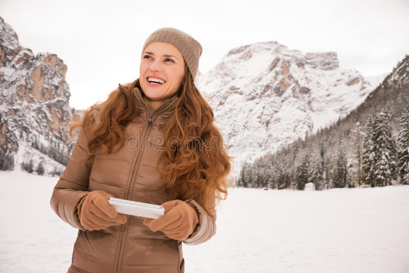 Woman with cell phone outdoors among snow-capped mountains stock images