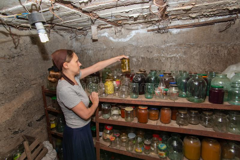 A woman in a cellar with food prepares supplies for the winter.  stock photo