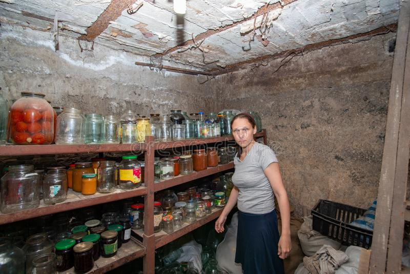 The woman in the cellar is gray-haired, the girl prepares food for the winter, canned food in glass jars on the rack.  stock images