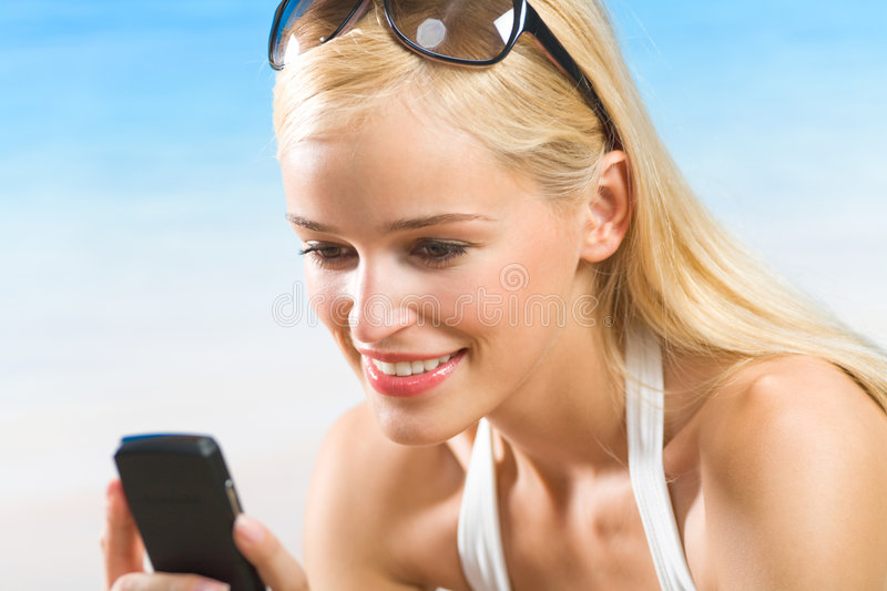 Woman with cellphone on beach. Young woman with cellphone on beach royalty free stock image