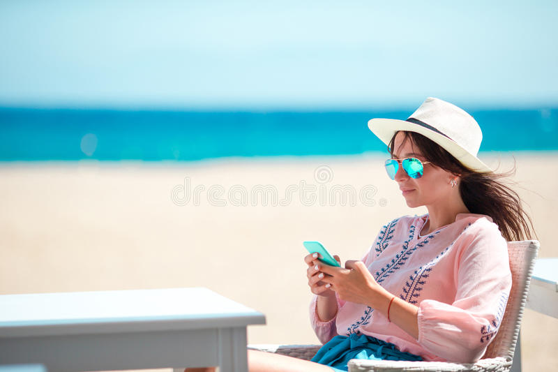 Woman with cellphone outdoors on the beach. Tourist using mobile smartphone. royalty free stock image