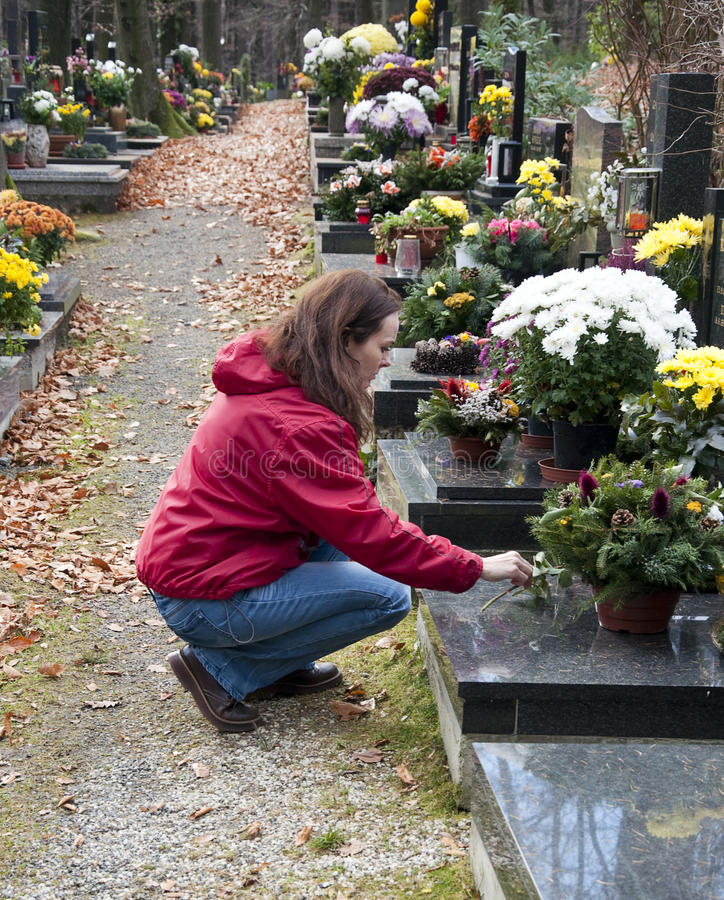 Woman at cemetery. Young woman crouching by a grave at cemetery; profile view stock photos