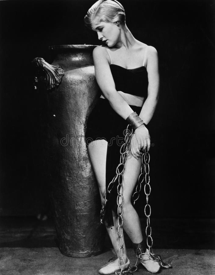 Woman chained in front of a big vase. (All persons depicted are no longer living and no estate exists. Supplier grants that there will be no model release royalty free stock images