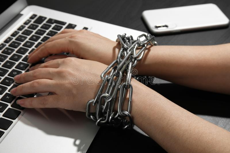 Woman with chained hands using laptop on black background. Loneliness concept stock photos