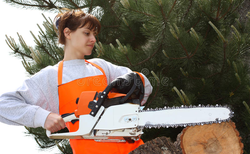 A woman with a chainsaw. A young woman with a chainsaw cutting lumber outdoor royalty free stock images
