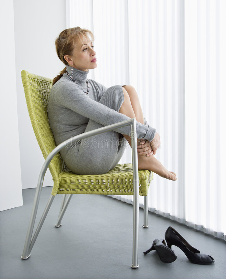 Woman in chair. Pretty Caucasian woman sitting with legs curled up in chair looking away stock photos