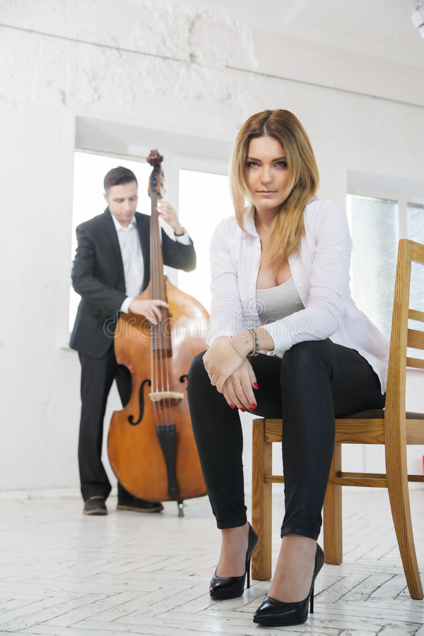 Woman on chair and man plays melody. Young women on stool and men plays melody royalty free stock images