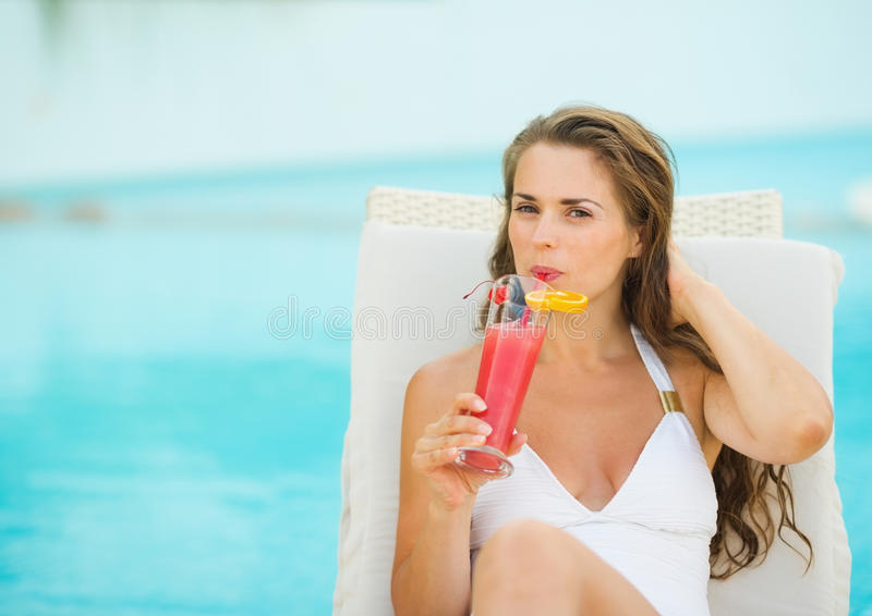 Woman on chaise-longue drinking cocktail. Young woman laying on chaise-longue and drinking cocktail stock image