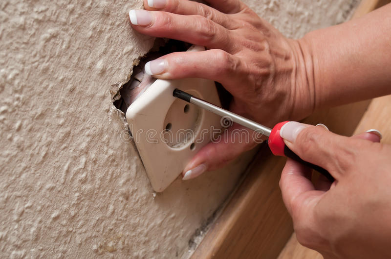 Woman changing a electrical outlet stock images