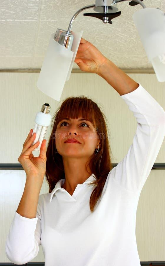 A woman changing light bulb stock photo