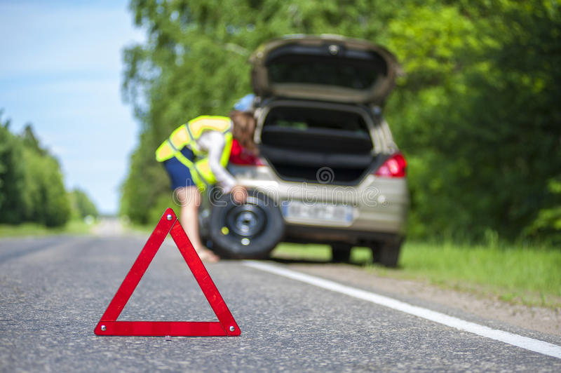 Woman changing tire after car breakdown royalty free stock photography