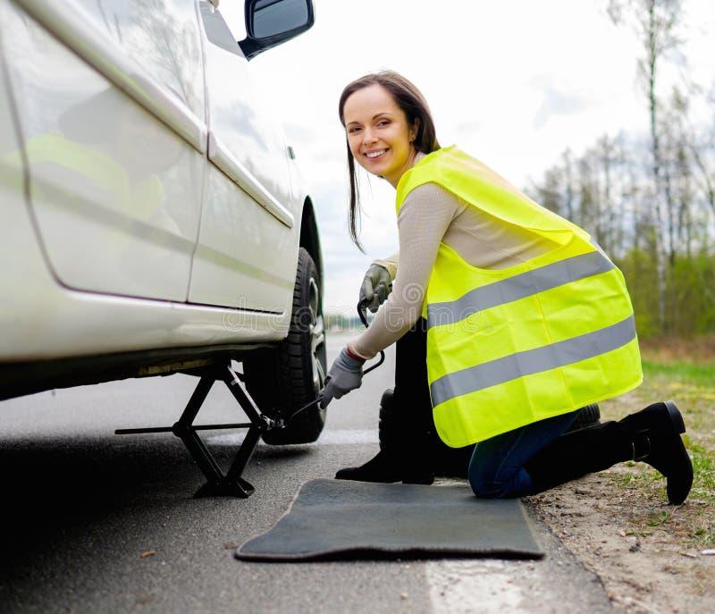 Woman changing wheel stock image
