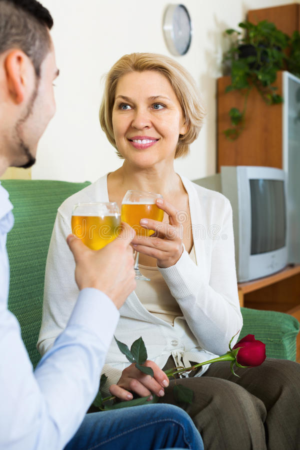 Woman chatting with young boyfriend. Happy blonde elderly women chatting with young boyfriend indoors stock photos