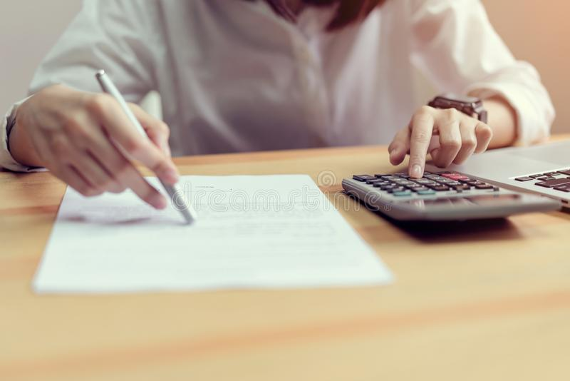 Woman check agreement documents and using calculator on table in office room. Woman check agreement documents and using calculator on table in office room, to stock photo
