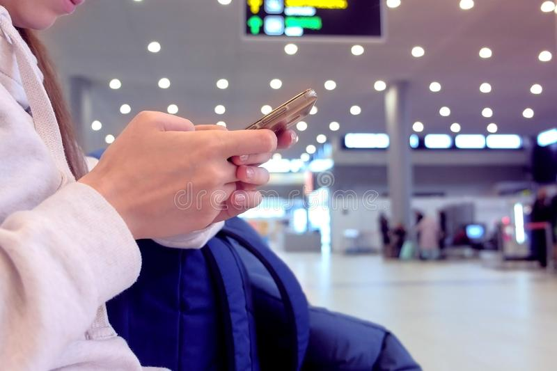 Woman check-in online registration on her mobile phone in airport hall, hands with smartphone close-up. stock photos