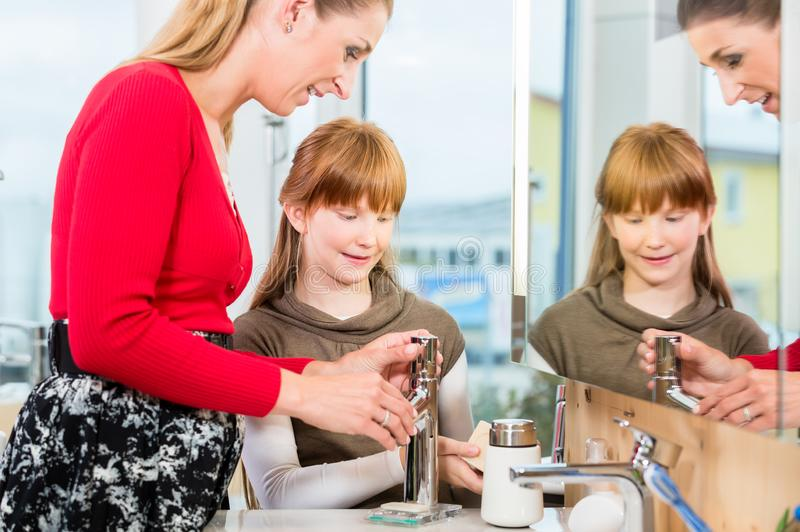 Woman checking a bathroom sink faucet in a modern sanitary ware shop. Side view of a women checking a bathroom sink faucet made of stainless steel, while stock photo