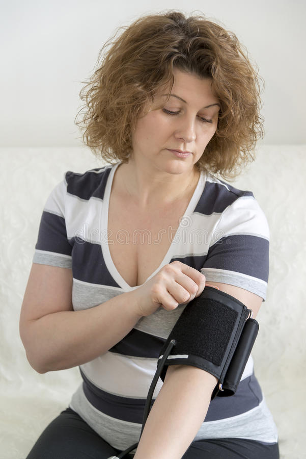 Woman checking blood pressure by tonometer. royalty free stock photo