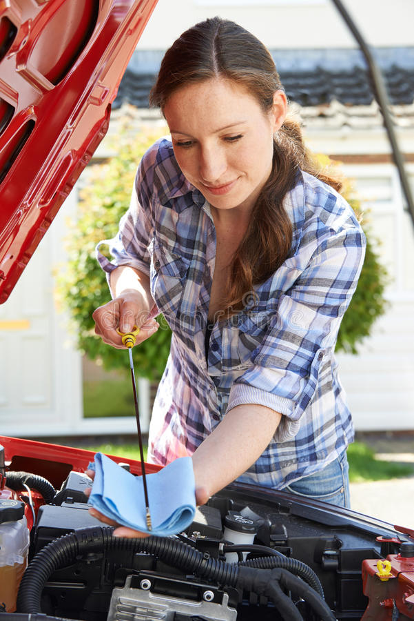 Woman Checking Car Engine Oil Level Under Hood With Dipstick stock photo