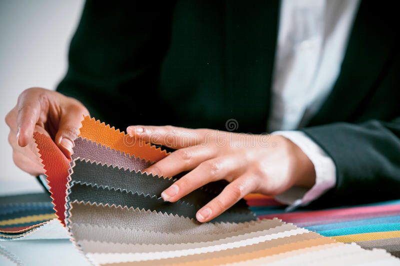 Woman checking fabric color swatches. Close up view of the hand of a woman checking fabric color swatches for interior decorating on a counter top royalty free stock image