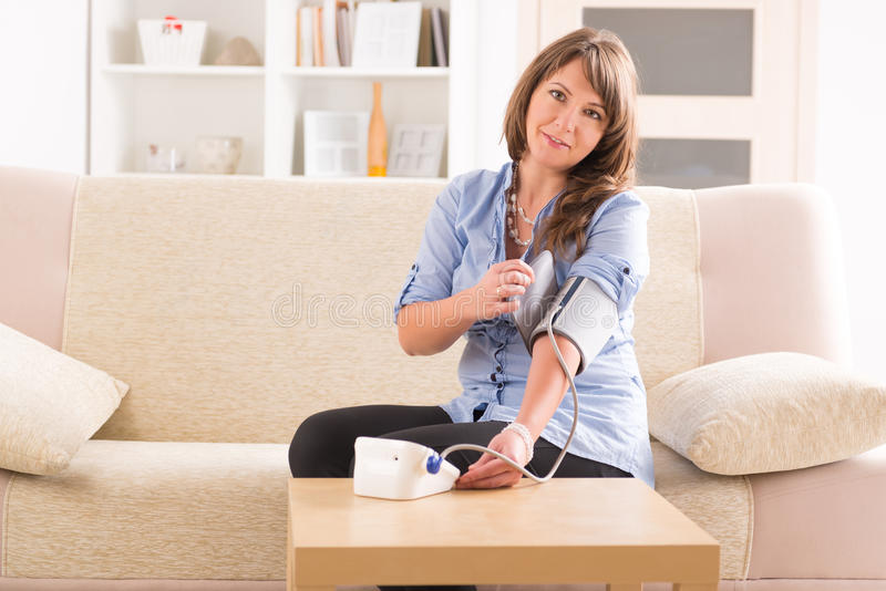 Woman checking her blood pressure. Beautiful woman checking her blood pressure at home stock photos