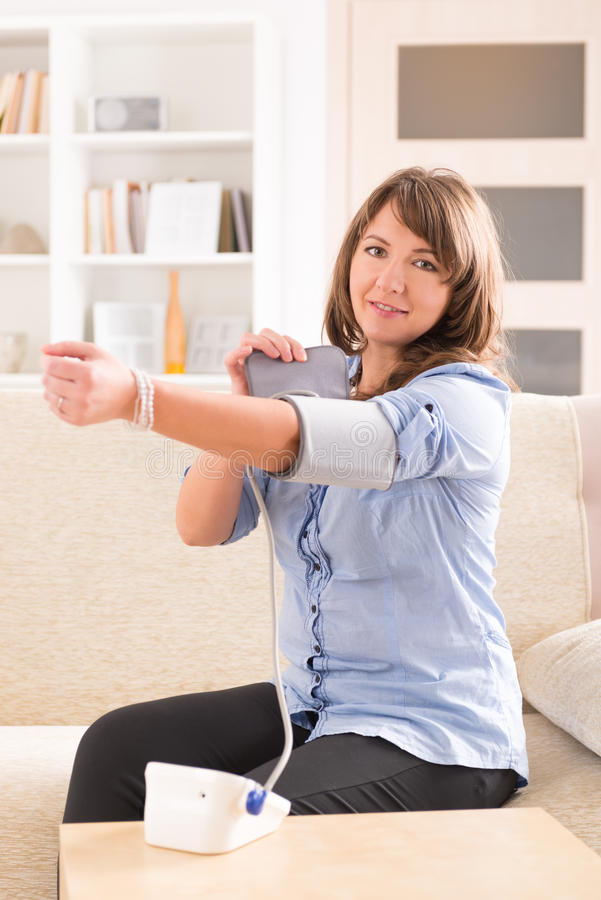 Woman checking her blood pressure. Beautiful woman checking her blood pressure at home stock image