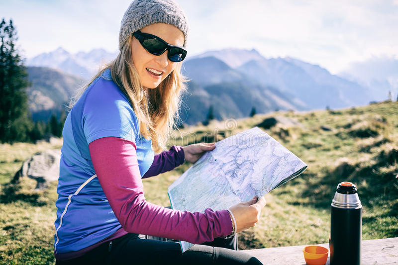 Woman checking map hiking in mountains stock photos